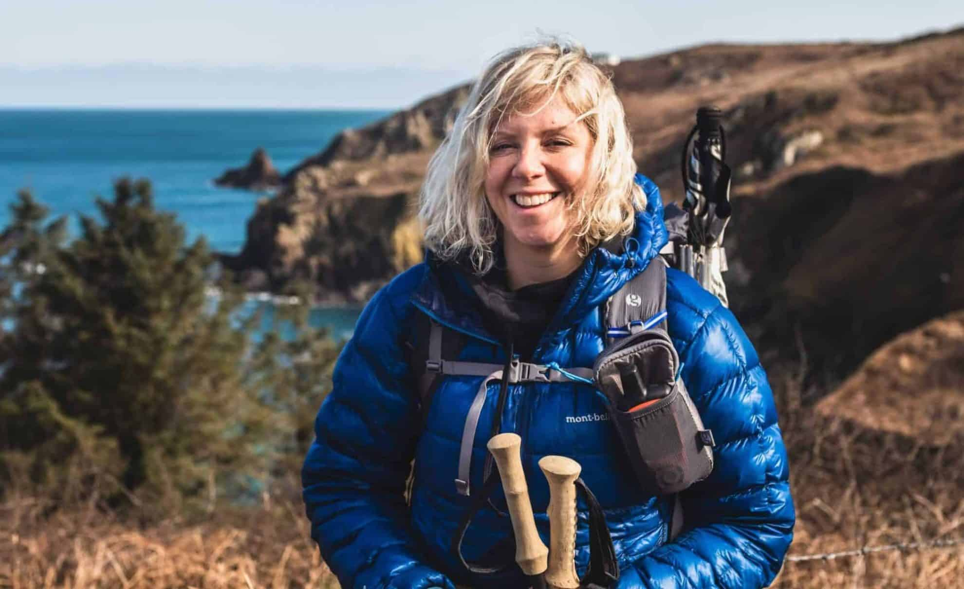 Gail in hiking gear with blue puffy, pack and poles on the South West Coast path with the sea behind