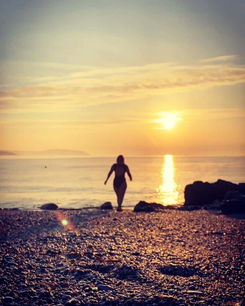 Woman walking into the sea for a swim as the sun sets