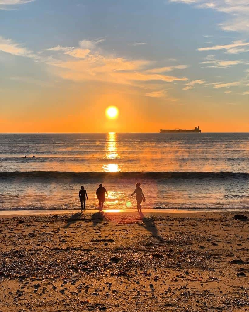 Three people in silhouette with the sea and sunset behind them
