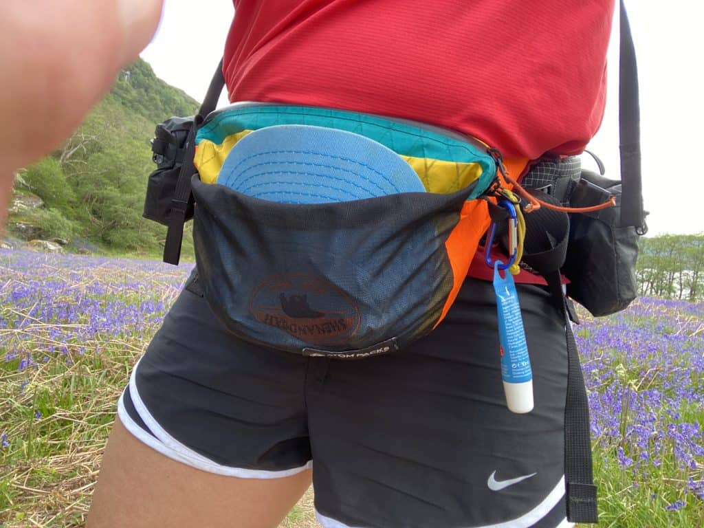 Close up of Gail wearing a brightly coloured atom fanny pack from a different angle